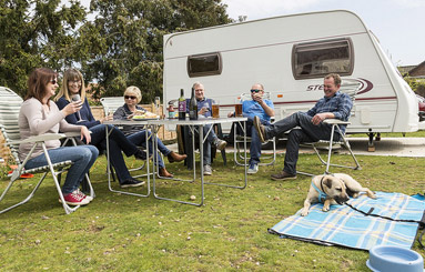 people having a drink outside their caravan